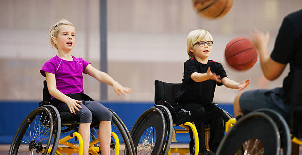 children in wheelchairs passing basketballs - wheelchair sports stock photos and pictures