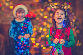 Little girl and boy in Christmas playing with lights