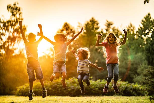 enfants sautant au coucher du soleil - nuage 6 photos et images de collection