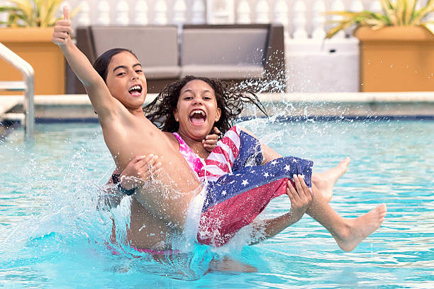 Children jumping into a swimming pool stock photo