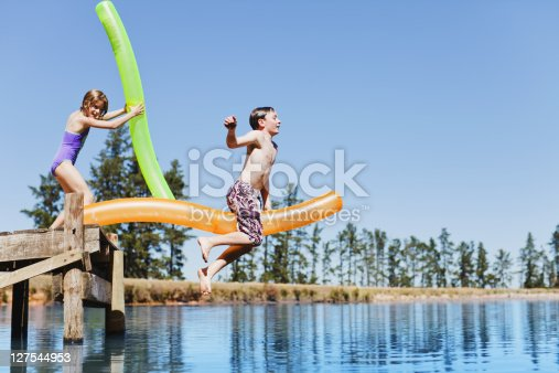 509813720 istock photo Children jumping into lake from jetty 127544953