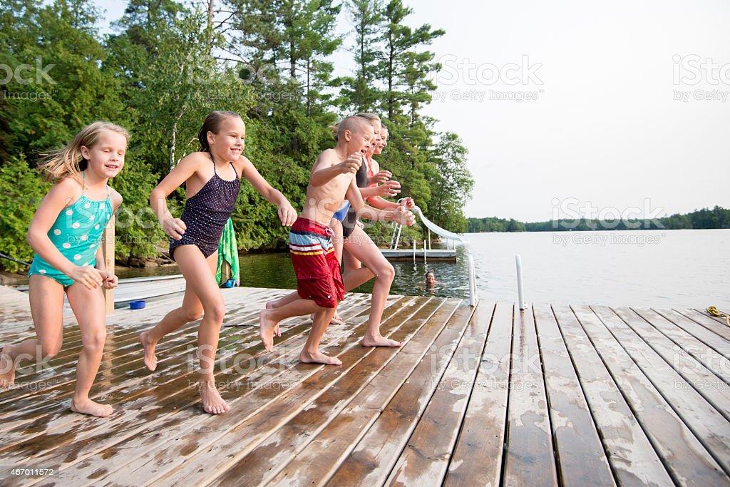 Children Jumping into Lake stock photo