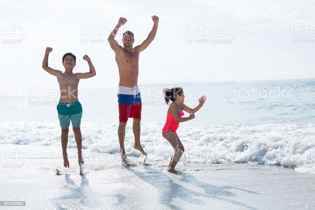 Children jumping with father at sea shore royalty-free stock photo