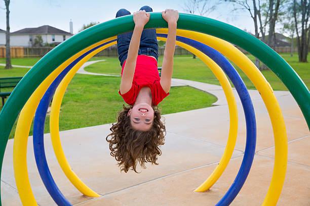 children kid girl upside down on a park ring - schommelen bungelen stockfoto's en -beelden