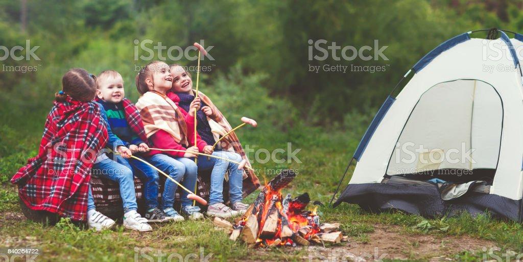 Enfants rire et faire revenir les saucisses sur le bûcher près de tente - Photo