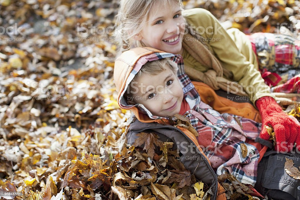 Children laying in pile of autumn leaves royalty-free stock photo