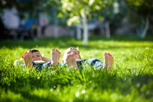 çim döşeme çocuk. bahar park aile pikniği - yatmak stok fotoğraflar ve resimler