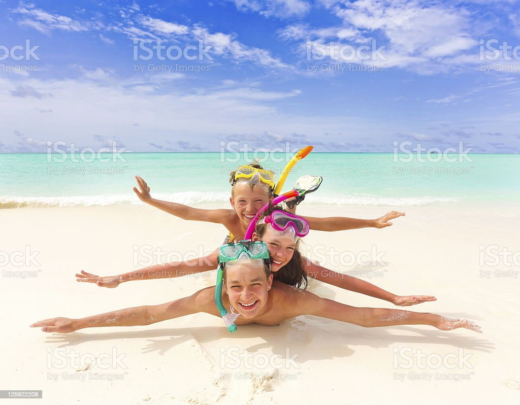 Children laying on top of each other on beach stock photo