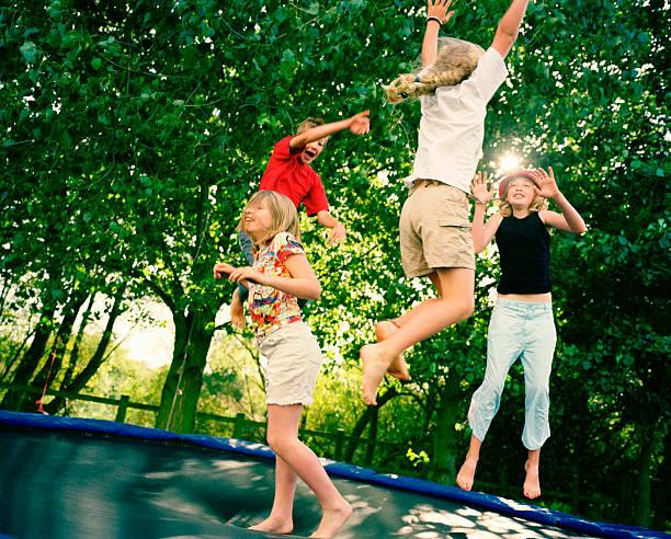 cuatro niños del salto del sobre trampolín - trampolín artículos deportivos fotografías e imágenes de stock
