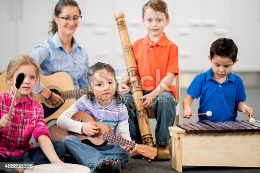A multi-ethnic group of children, playing instruments together in a daycare setting, with a teachers help.