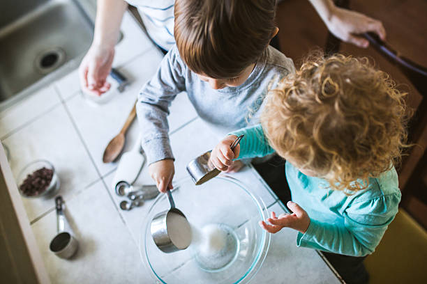 Children Learning to Bake To toddler age kids learn to bake and cook together, each child helping to measure and pour out the ingredients.  An enriching time of discovery for 2 and 3 year olds.  Horizontal image. dry measure stock pictures, royalty-free photos & images