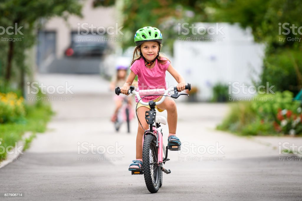 Children learning to drive a bicycle on a driveway outside. stock photo