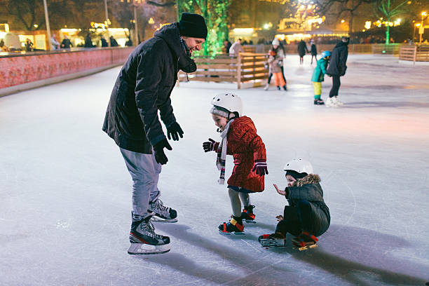 Children learning to Ice-skate Photo of a little boy and his sister learning how to ice-skate on Ice rink. While their father is showing them basic positions, little boy fell down. ice skating stock pictures, royalty-free photos & images
