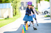 Children learning to roller skate on the road with cones. Twin girls are practising safe roller skating on a home driveway road wearing protective gear - helmets, knee, elbow and hand protectors or pads.