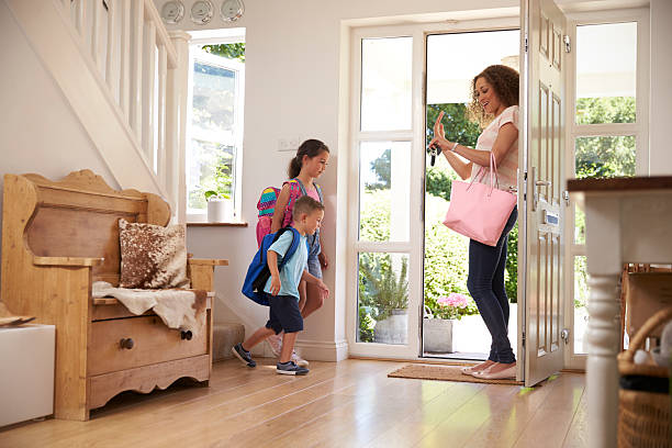 Children Leaving Home For School With Mother - foto stock