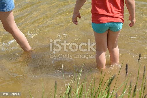 Children legs barefoot resting on a water lake summer landscape