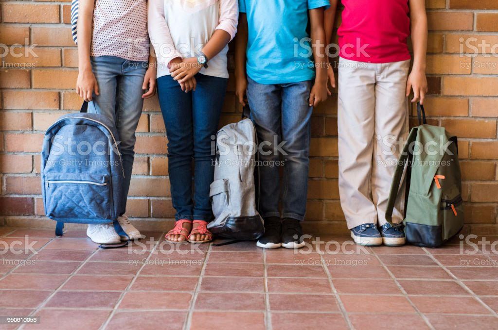 Children legs with backpacks at school stock photo