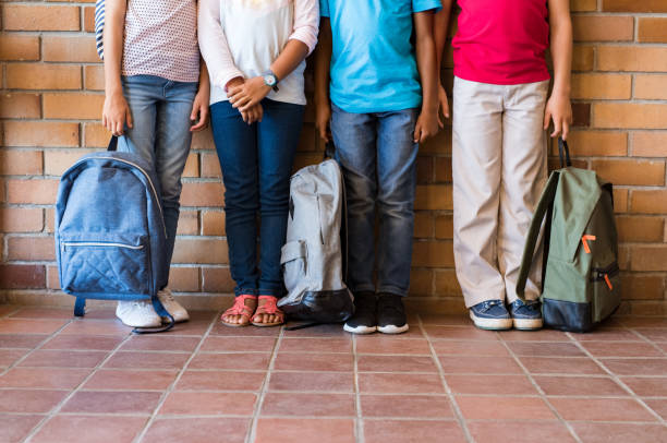 Children legs with backpacks at school - foto stock