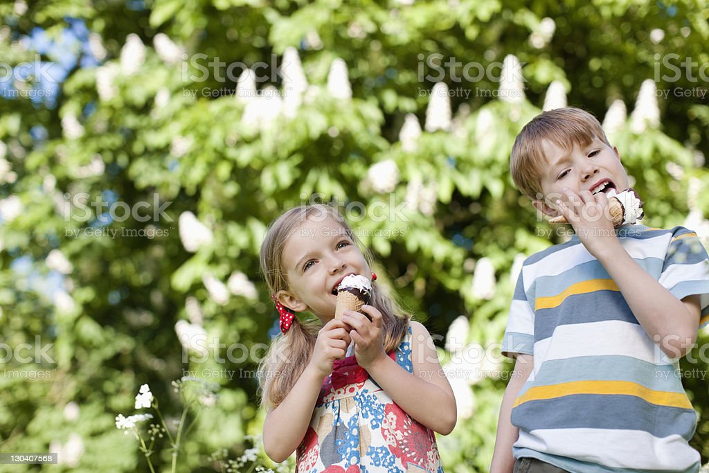 Children licking ice cream outdoors stock photo