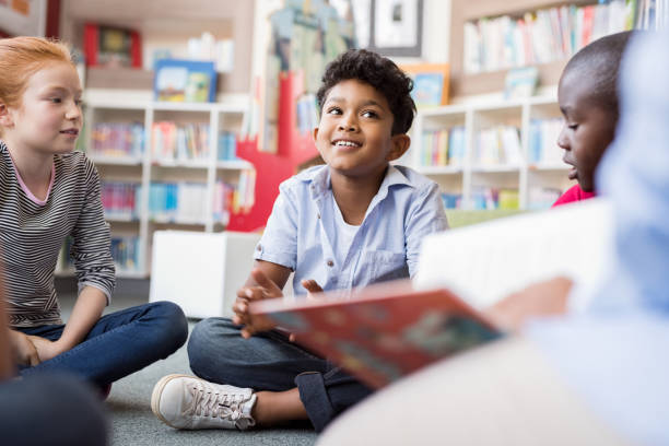 Children listening stories Multiethnic group of kids sitting on floor in circle around the teacher and listening a story. Discussion group of multiethnic children in library talking to woman. Portrait of smiling hispanic boy in elementary school. elementary age stock pictures, royalty-free photos & images
