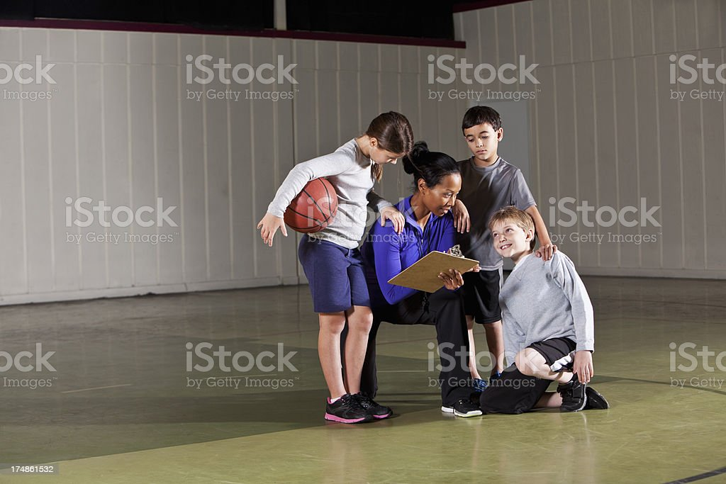 Children listening to basketball coach stock photo