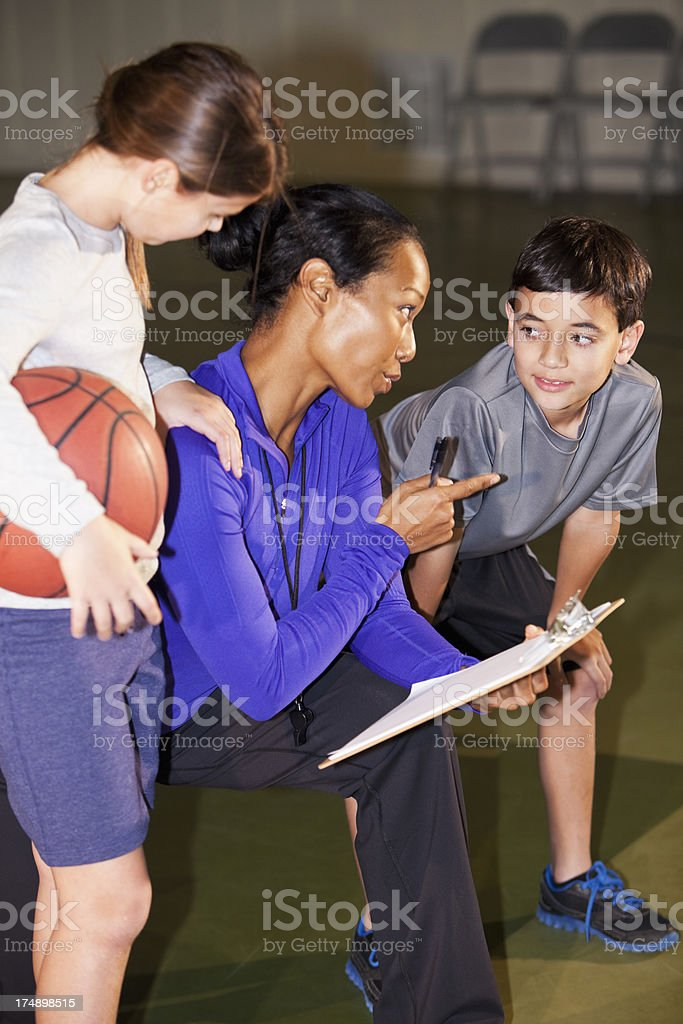Children listening to basketball coach royalty-free stock photo