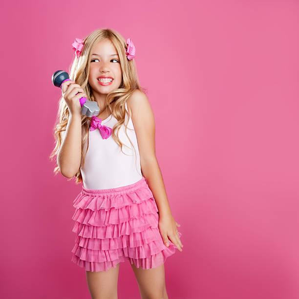 kinder sterne wenig sängerin wie modepuppe mit mikrofon - barbiekleidung stock-fotos und bilder