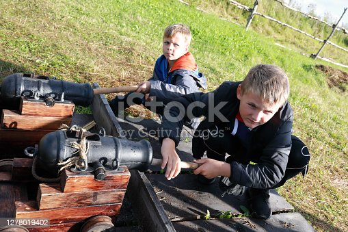 Children load signal ancient cannons in summer