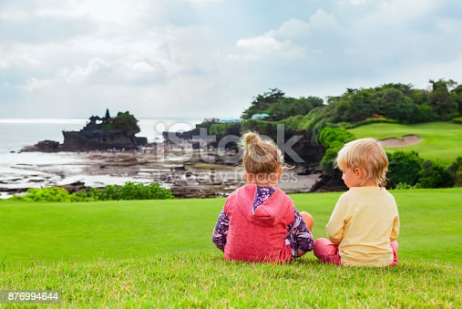 929671306 istock photo Children look from high cliff at Balinese temple Tanah lot. 876994644