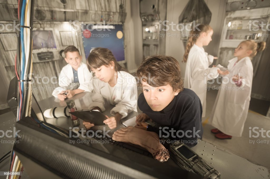 Children looking for a clue in the bunker quest room stock photo