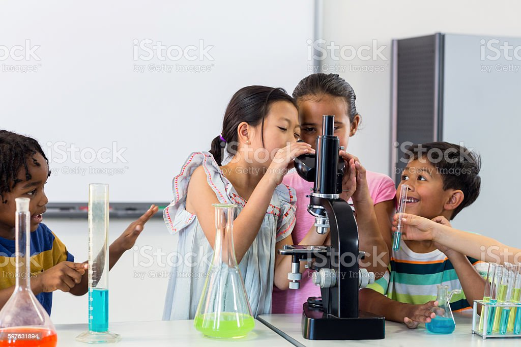 Children looking in microscope stock photo