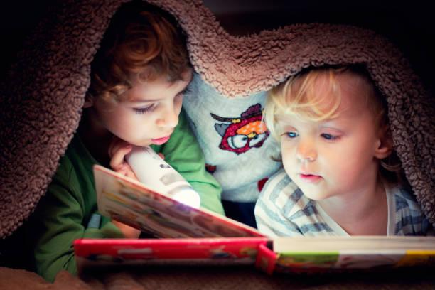 kinder suchen in das buch unter der decke - deckenleuchte kinderzimmer stock-fotos und bilder