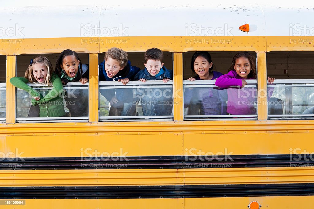 Children looking out school bus window stock photo
