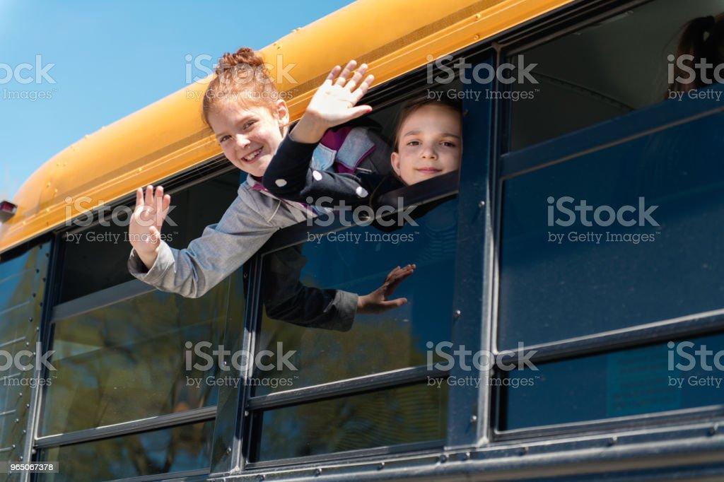 Children looking out school bus window zbiór zdjęć royalty-free