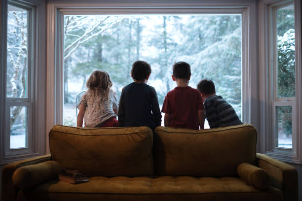 Children Looking Out the Window At Falling Snow