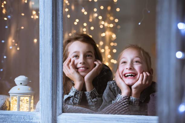 kinder, schaut aus dem fenster - weihnachten 7 jährige stock-fotos und bilder
