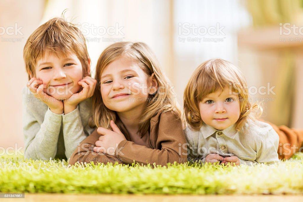 Children lying down on carpet. stock photo