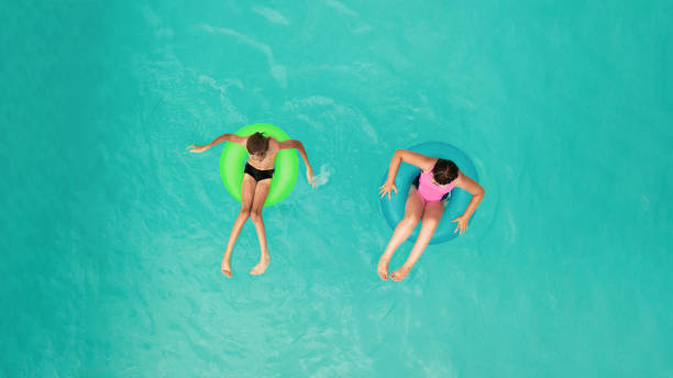 children lying in inflatable rings - children play water park stock photos and pictures