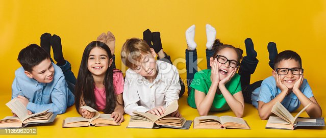 istock Children lying on floor and reading books 1135962012