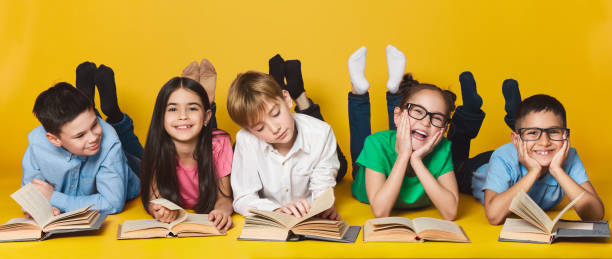 crianças que encontram-se no assoalho e em livros de leitura - reading - fotografias e filmes do acervo