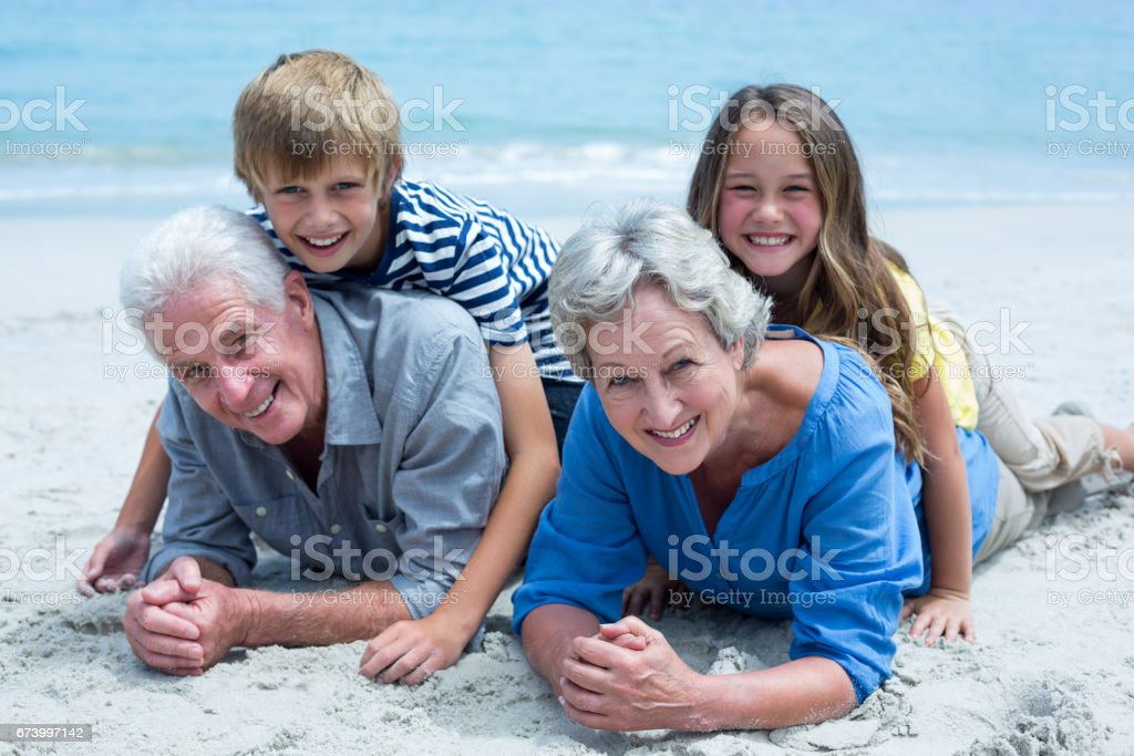 Children lying on grandparents at sea shore royalty-free stock photo