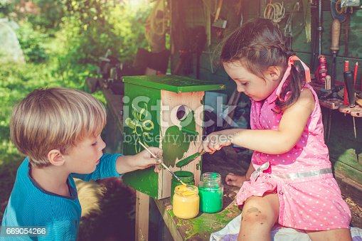 Little boy and girl building and painting birdhouse outdoors in summer