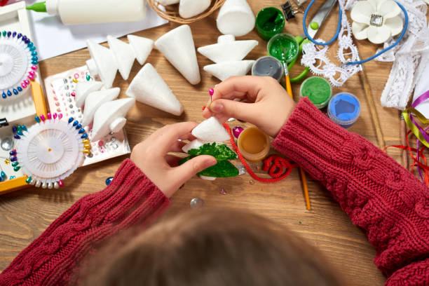 kinder machen handwerk und spielzeug, weihnachtsbaum und andere. malerei aquarelle. ansicht von oben. kunst am arbeitsplatz mit kreativen accessoires. flache laien malwerkzeuge. - basteln mit kindern weihnachten stock-fotos und bilder