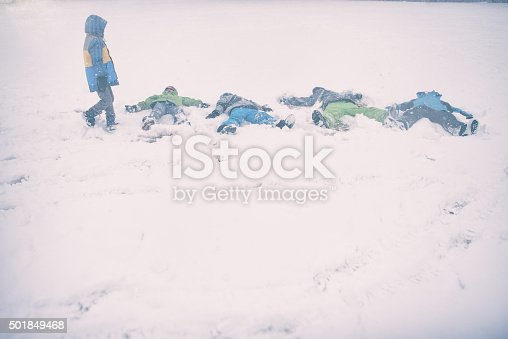 865399512istockphoto Children make snow angles on a storm day 501849468