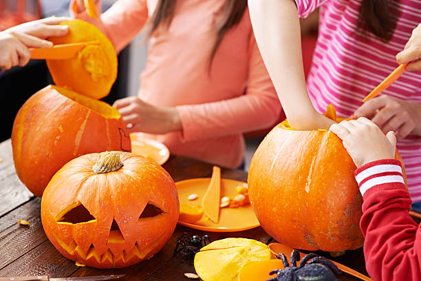 Children making Halloween pumpkin decoration for people stock photo