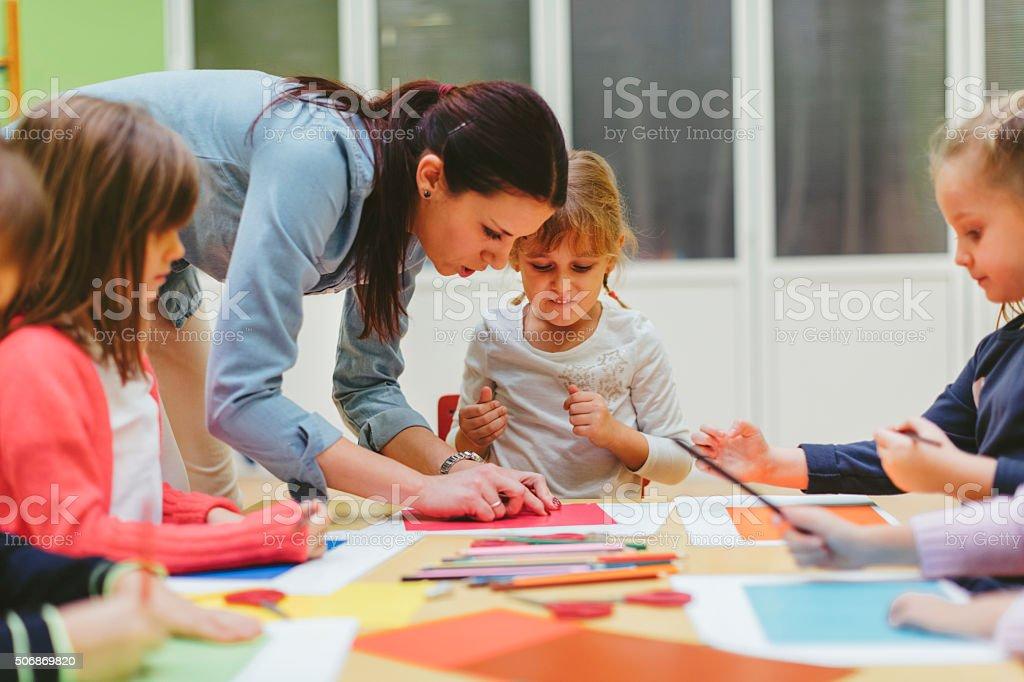 Children making origami in a preschool stock photo