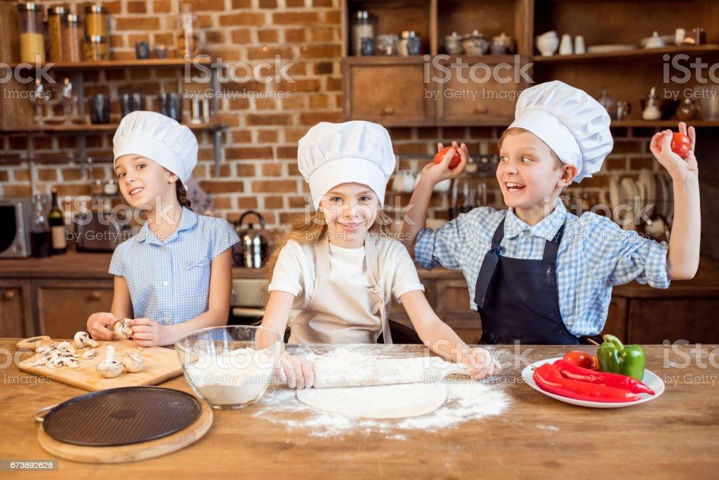 enfants faire la pâte à pizza et préparer les ingrédients de la pizza dans la cuisine photo libre de droits
