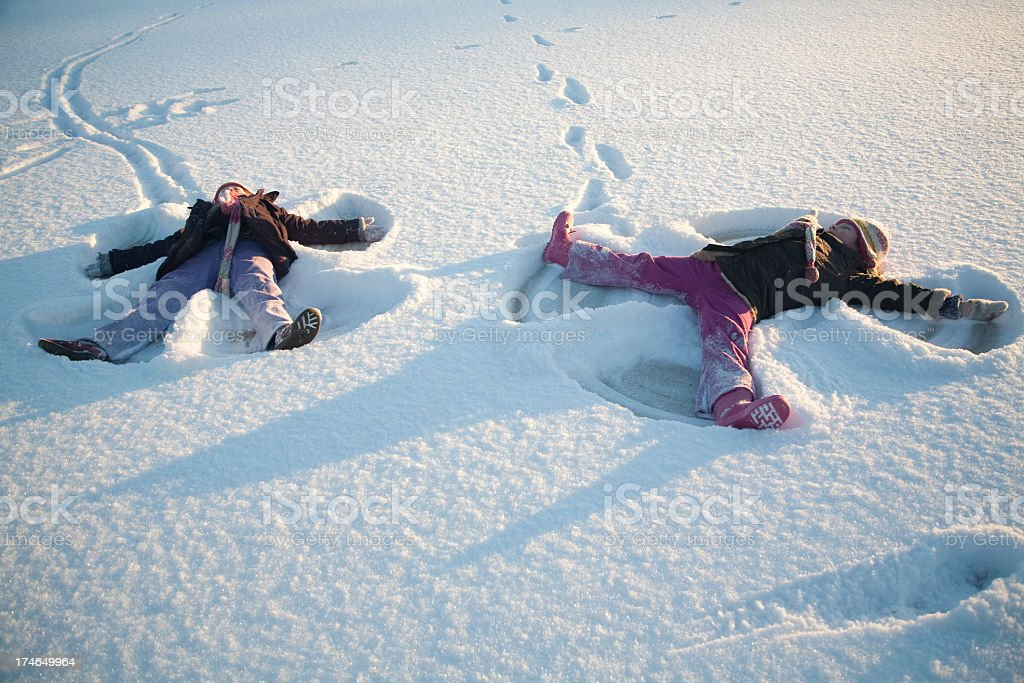 Children making snow angels in the snow stock photo