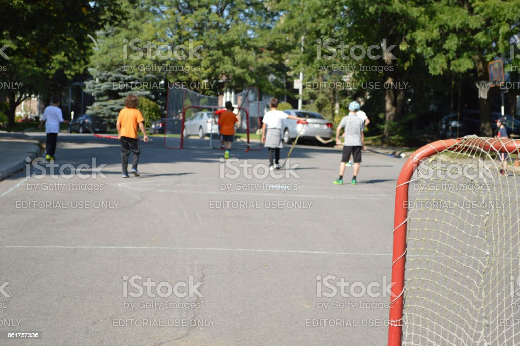 Neighborhood friends improvising a street hockey game after school to...
