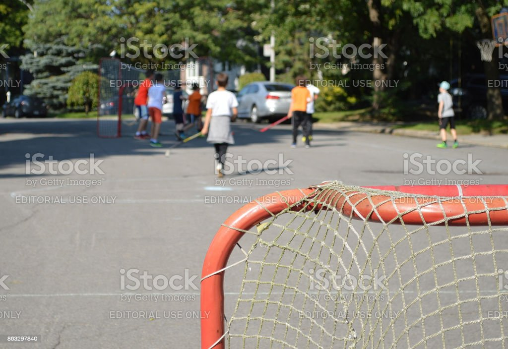 A group of teenagers are making sports by playing a street hockey...